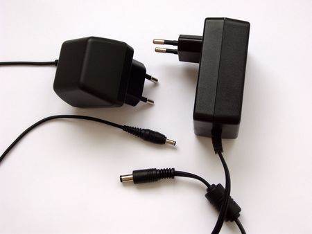 Two black charging apparatus with black cables and couplings, on white. (stock photo)