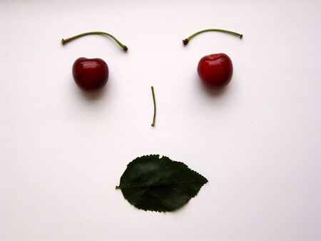 Face made from cherries, leaf and stalks, isolated. (stock photo)