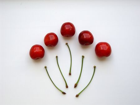 Five red cherries and detached stalks, isolated on white. (stock photo)