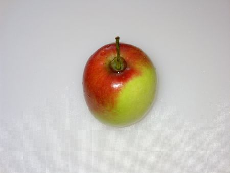 Red and green coloured apple fruit with stalk and water drops, standing, isolated on light grey. (stock photo)