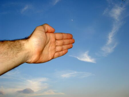 Left hand with all fingers ahead raised toward the blue sky between clouds. (stock photo)