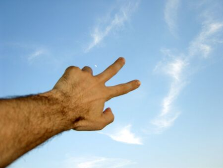 Left hand with two fingers ahead raised toward the blue sky. (stock photo) Stock Photo