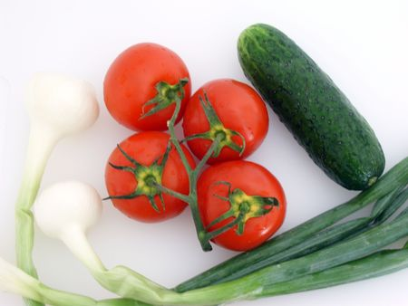 Vegetables: four tomatoes on a branch, green onions, one green cucumber, on white. (stock photo)