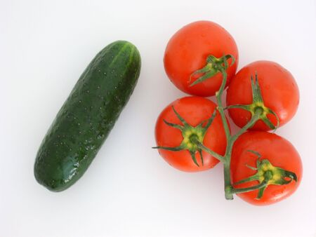 Vegetables: four red tomatoes on a branch and one green cucumber, isolated on white. (stock photo)