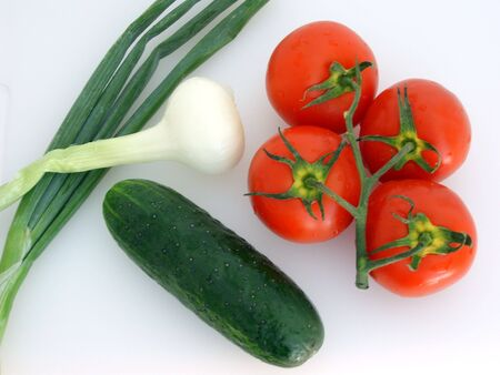 Vegetables: four tomatoes on a branch, two green onions, one green cucumber, on white. (stock photo)