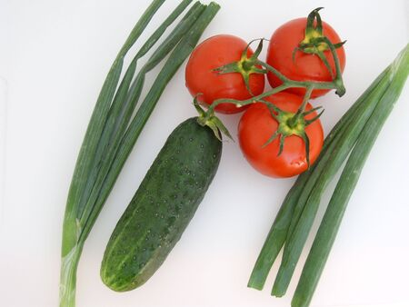 Vegetables: three tomatoes on a branch with a green cucumber, two green onions, on white. (stock photo) Stock Photo