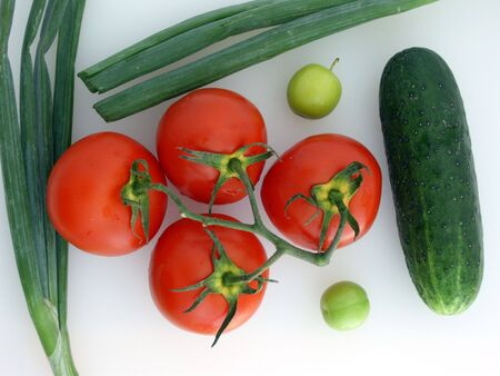 Vegetables: four tomatoes on a branch, two green onions, green cucumber, two green wax cherry fruits, on white. (stock photo)
