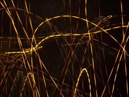 Orange light traces in the dark. Unique trail forms in the night by photographic technique. Stock Photo