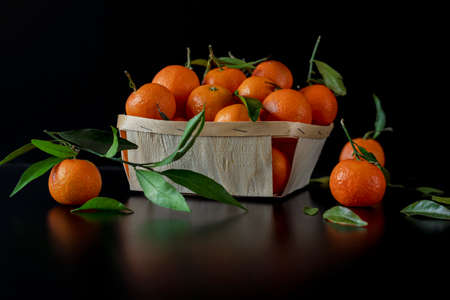 Tangerines, oranges, mandarins, clementines, citrus fruits with leaves in a wooden basket. Black background. Side view Stock Photo