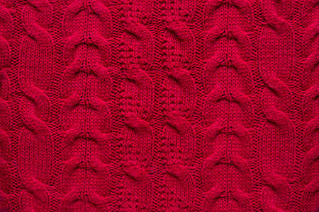 The texture of a red knitted sweater. Textured background knitting.