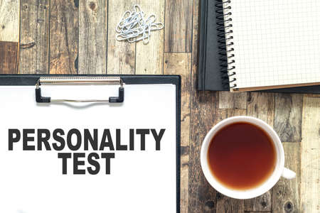 Text written on white paper, personality test. The sheet is on a wooden table, next to it is a cup of tea and a notebook. Business concept for relationship assessment Banco de Imagens