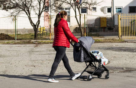 Young mother with baby stroller on the street.