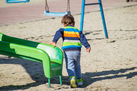 Little boy dressed in colorful clothes plays in the playground. The child plays on the slide. Rear view.