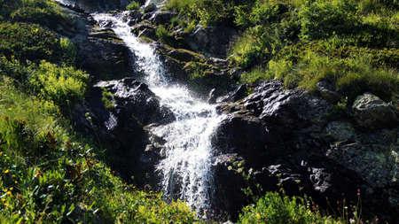 rare rocks: The beautiful mountain waterfall among the rocks in a wild place,