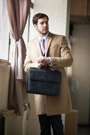Classic and elegant businessman wearing beige coat and holding a black briefcase looking to his left side. photo