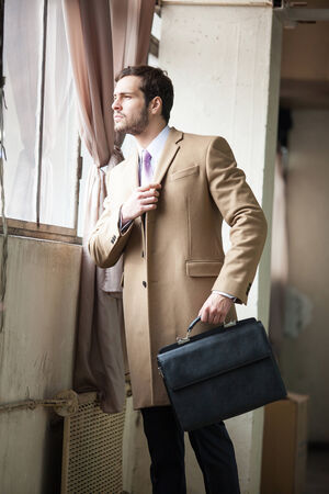 Elegant young fashion man holding one hand on his lapel coat while looking out the window. photo