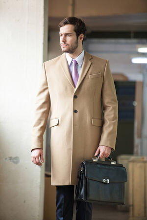 Serious and young business man is walking and looking away from the camera while holding a black suitcase. photo