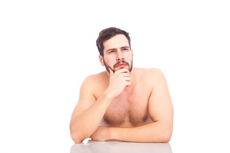 half-naked beautiful man sitting at white table and thinking, on white background  photo