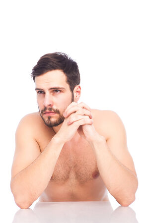 concerned man without shirt at white table on white background with reflexion photo