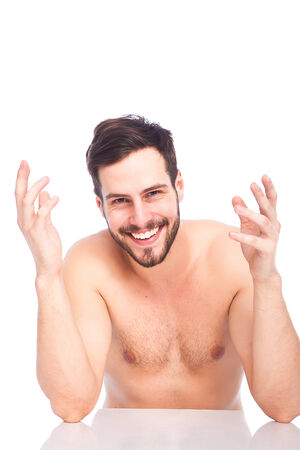 smiling man without shirt at white table on white background photo