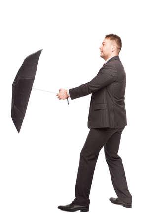 speaking tube: elegant businessman using his umbrella to defend Stock Photo