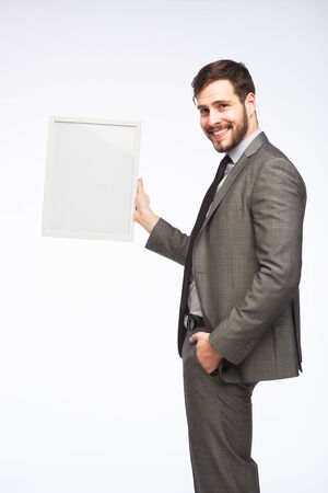 businessman in an elegant suit showing a framed board photo