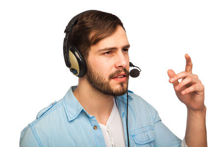 Closeup portrait of male customer service representative or call centre worker or operator or support staff speaking with head set, isolated on white background and pointing to copy space photo