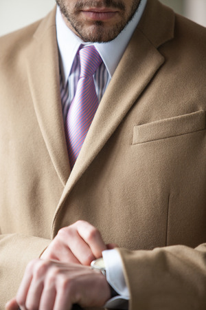 Close up of businessman in beige coat, white chemise with stripes and pink tie photo