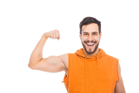 smiling young man showing his muscles on white background
