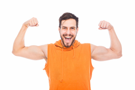 strong energic man showing his muscles on white background