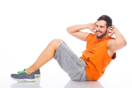 young man doing exercises on the floor on white background with reflexion Stock Photo
