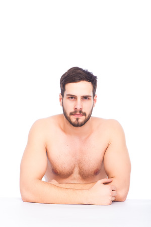 serious half-naked man at an white table on white background photo
