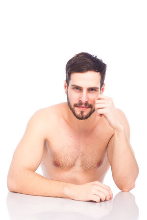 half-naked beautiful man with beard sitting at white table, isolated photo
