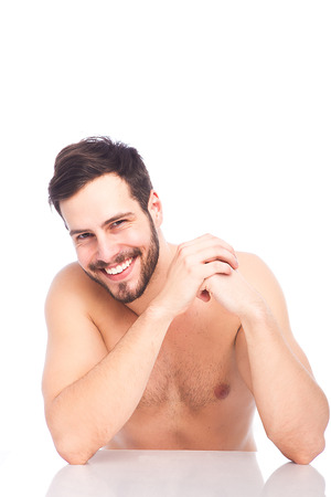 nice smile of handsome man sitting at white table without shirt Stock Photo
