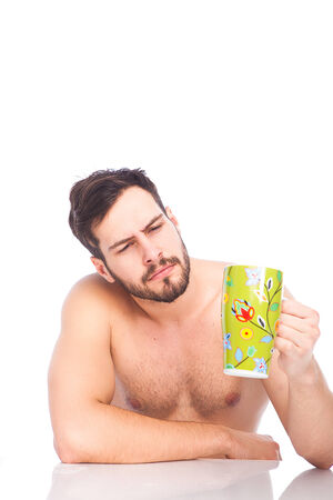 handsome man in the morning without shirt looking at his cup of coffe  photo