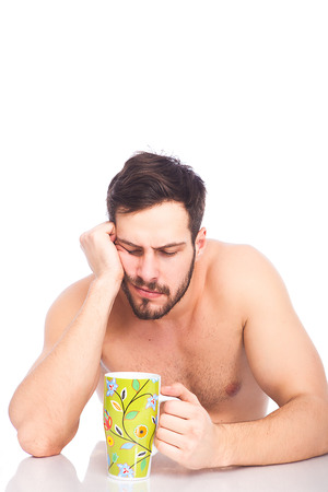 sleepy hangover man without shirt with a cup of coffe on white background  photo