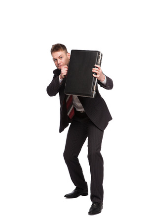 elegant businessman using his briefcase to defend himself on white background Banco de Imagens