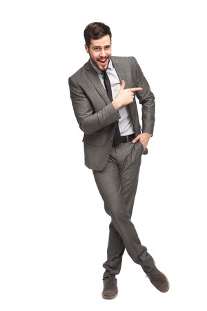 elegant man in grey suit pointing in one direction on white background