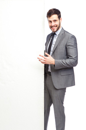 elegant man smiling after a panel advertise on white background