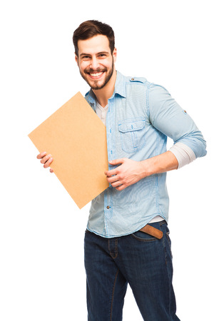 Young expressive handsome man casual dressed smiling and showing a wooden blank panel on white background Standard-Bild