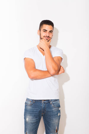 atractive: handsome hispanic man in white tshirt, with shadow on white background