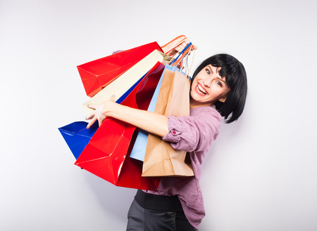 happy young woman with a lot of shopping bags in her arms Banque d'images