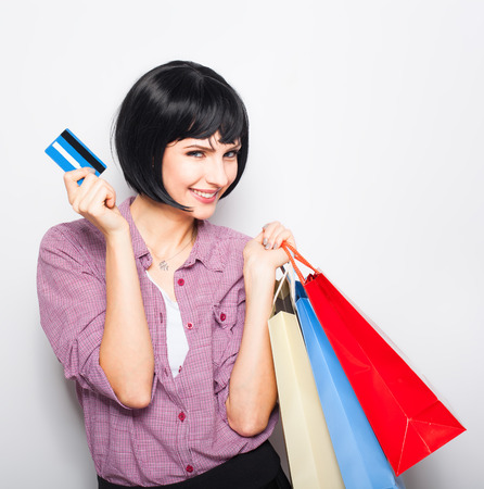 young beautiful woman having shopping colored bags over shoulder and credit card in hand