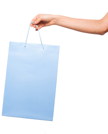 blue shoping bag signifying gift or shopping holded by a woman hand on white background