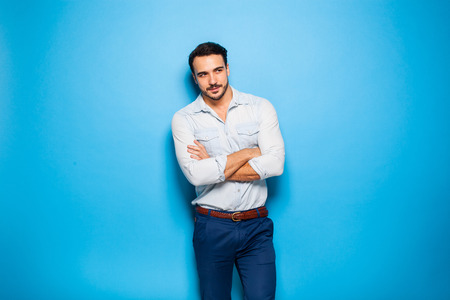 self assured: handsome man looking in one direction with arms folded on blue background