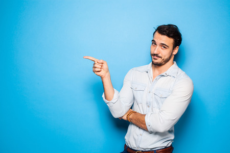 thirties portrait: handsome man with beard pointing in one direction on a blue background Stock Photo