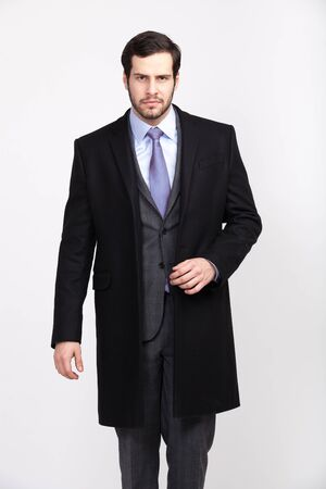 handsome elegant man with beard in black overcoat, isolated