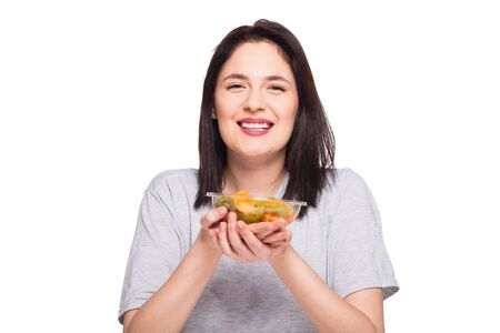 heaving: beautiful woman smiling and heaving a healthy fruits meal with orange and kiwi, isolated on white