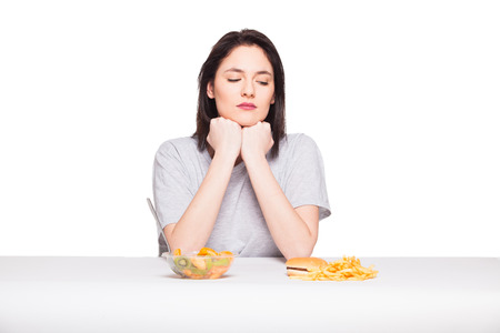 healthy versus junk food concept with a natural woman heaving in front fruits meal and fries with hamburger, isolated on white
