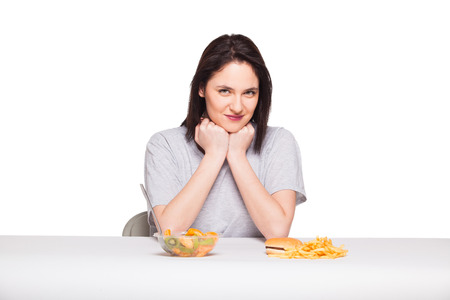 heaving: healthy versus junk food concept with a natural woman heaving in front fruits meal and fries with hamburger, isolated on white